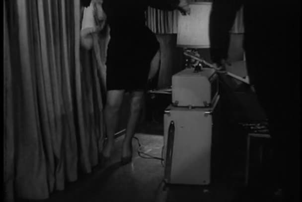 Medium shot of woman in slit dress dancing into room, 1960s