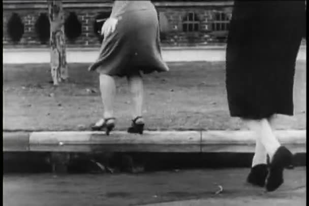 Two women jumping over puddle and then splashed by car, 1940s