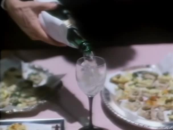 Waiter pouring champagne into glass at elegant party,1980s