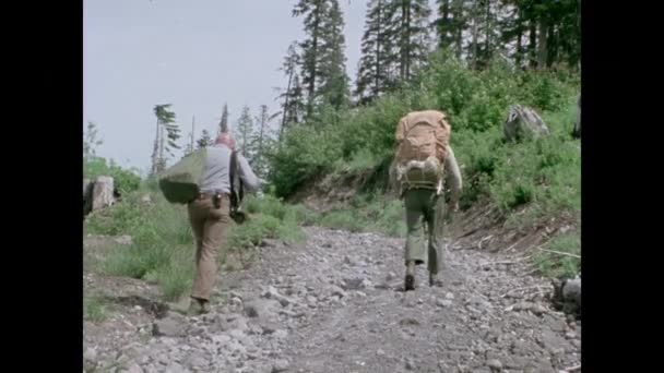 Two men with backpacks hiking up dirt road, 1970s