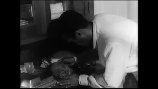 Man picking up nails from a pile on kitchen counter, 1960s