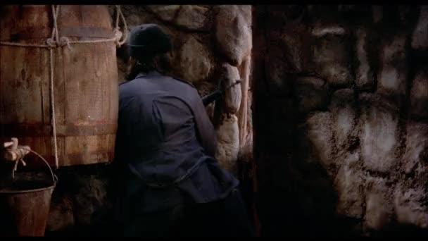Mann Gewehr schießen, durch eine Lücke zwischen den Wänden in Kabine, 1970er Jahre