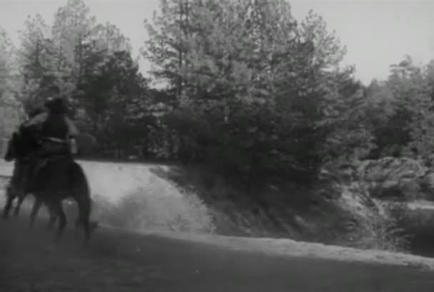 Skupina kovbojů tryskem na koních v krajině, v roce 1930