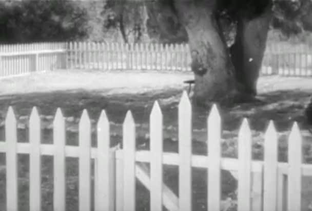 Woman walking into yard through white picket fence, 1930s