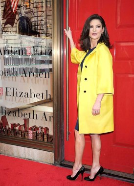 Catherine Zeta-Jones (wearing a Gucci coat, Oscar de la Renta dress, and Brian Atwood heels) at in-store appearance for Elizabeth Arden RED DOOR Global Flagship Store Ribbon Cutting, Elizabeth Arden RED DOOR Fifth Avenue Store, New York, NY, March 06