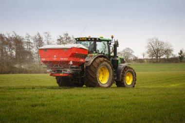 Buckingham, UK - March 22, 2018. A John Deere tractor sprays crops in spring in the Buckinghamshire countryside