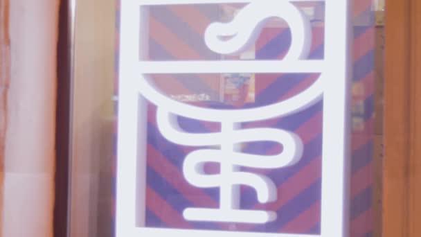 Zeichen der Medizin mit Schlange, Schaufenster der Apotheke leuchtet