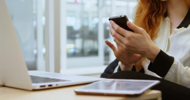 Young female executive using mobile phone in office 4k