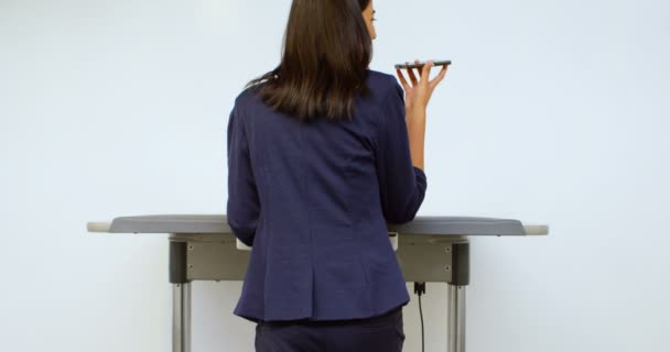 Rear view of female executive talking on mobile phone while exercising on treadmill 4k