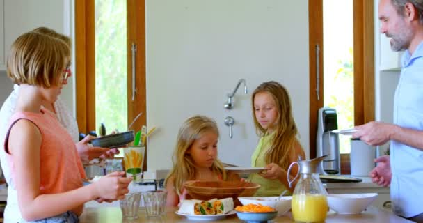 Family having meal in kitchen at home 4k