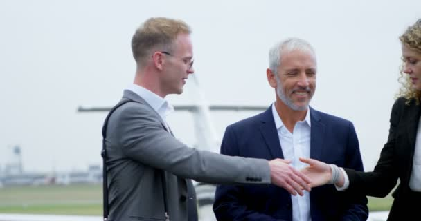 Business people shaking hands with each other on a runway 4k