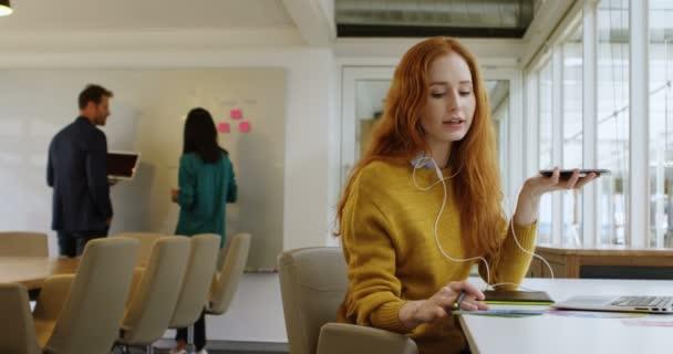 Female graphic designer talking on mobile phone at desk in office 4k
