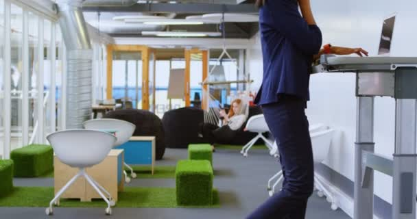 Female executive talking on mobile phone while exercising on treadmill in office 4k