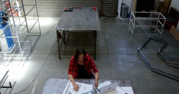 Female welder working at desk in workshop 4k