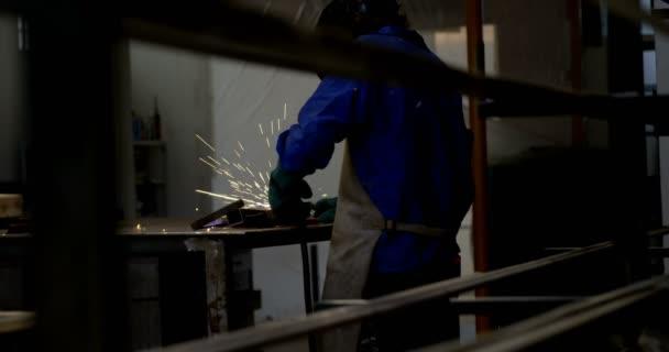 Female welder using blowing torch on a rod in workshop 4k