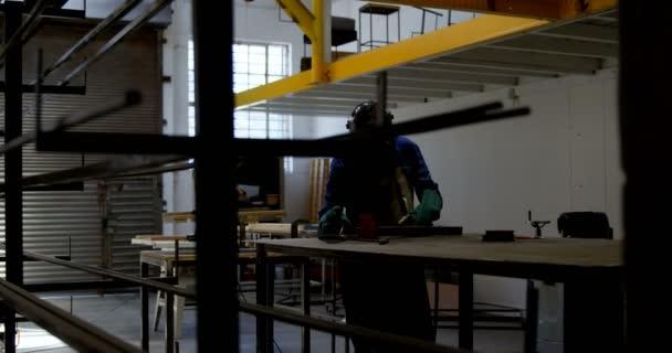 Female welder using blow torch on a rod in workshop 4k
