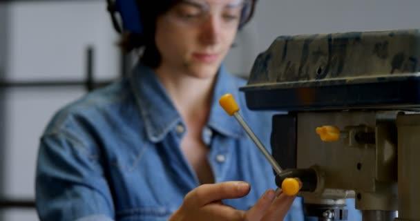 Young female welder using drill press machine in workshop 4k