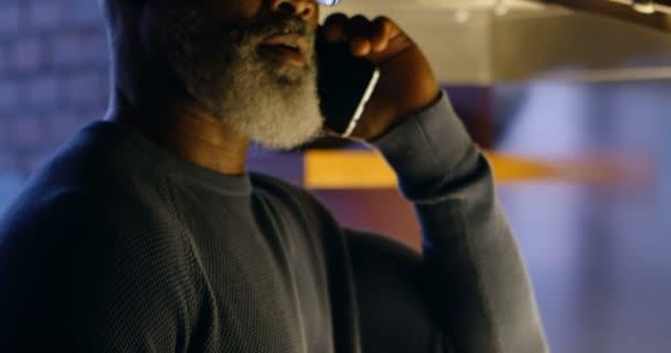 Senior man talking on mobile phone in kitchen at home 4k