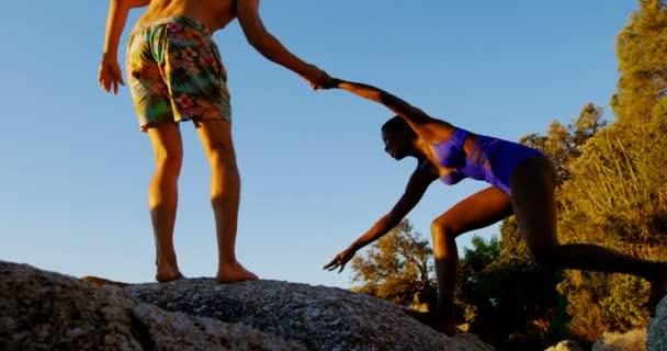 Muž dává pomocnou ruku k ženě za podporu v beach 4k