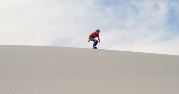 Man sand boarding on the slope in desert on a sunny day 4k