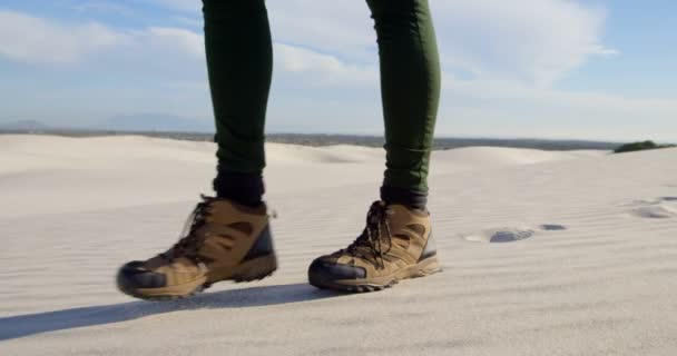 Woman in sports shoes walking in the desert on a sunny day 4k