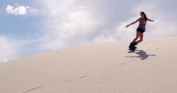 Woman sand boarding on the slope in desert on a sunny day 4k