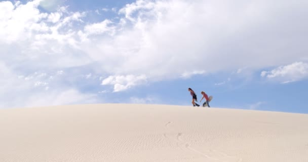 Couple with sand boards walking on the sand dune on a sunny day 4k