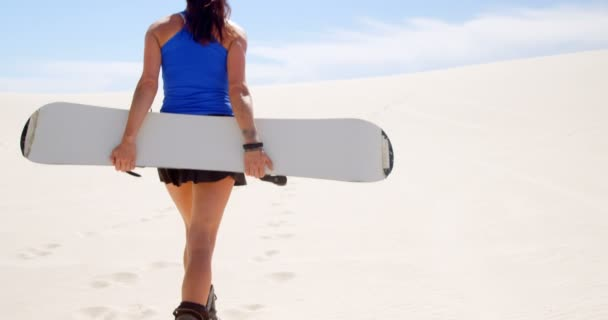 Rear view of woman walking with sand board in the desert 4k