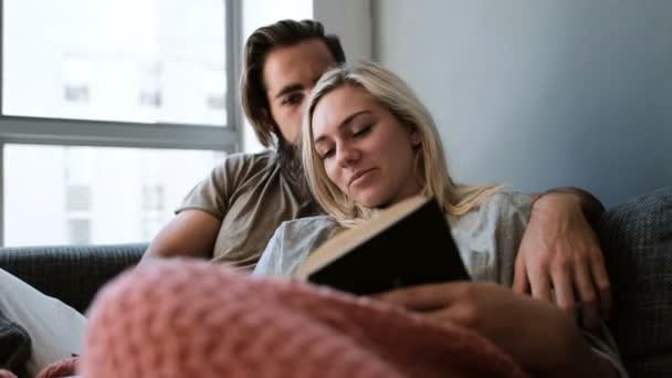 Couple reading a book in living room at home 4k