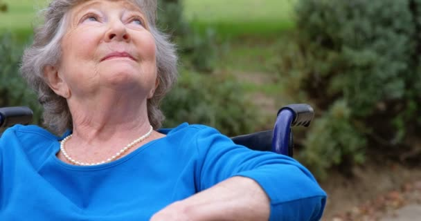 Thoughtful senior woman sitting on wheelchair outdoors 4k