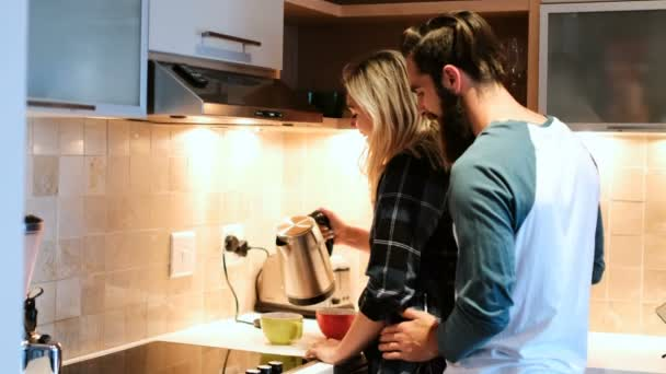 Couple interacting while having coffee in kitchen at home 4k