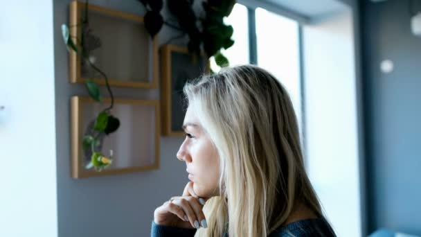 Thoughtful woman looking outside through window at home 4k