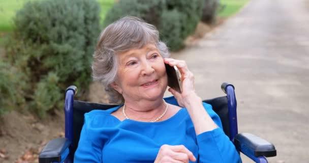 Smiling Senior woman talking on mobile phone on wheelchair 4k
