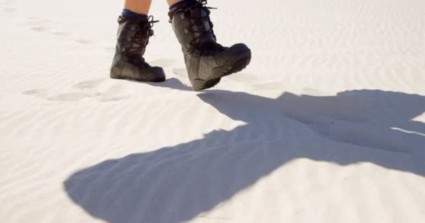Close-up of woman in boots walking in the desert on a sunny day 4k