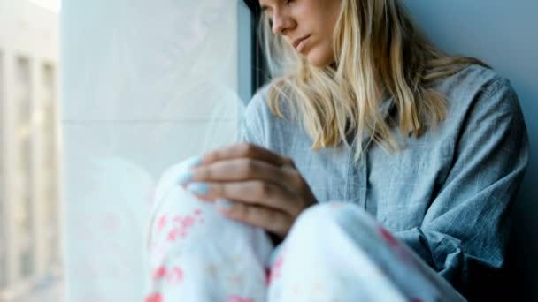 Worried woman sitting near window at home 4k