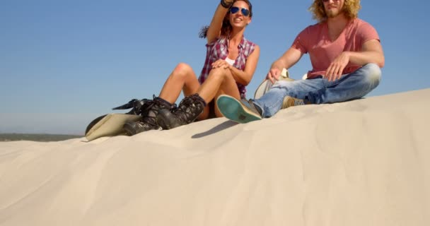 Couple with sand boards sitting and pointing at a distance in the desert on a sunny day 4k