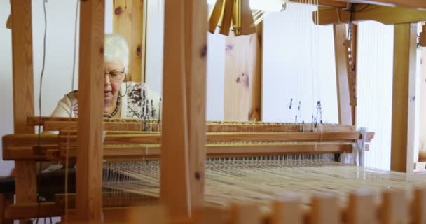 Front view of old caucasian senior woman weaving cloth on handloom machine  in a workshop  She is using cotton thread 4k