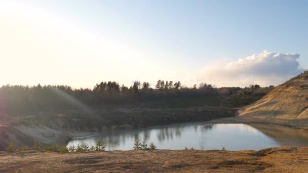 Ein großer sandiger Hügel und ein kleiner See darunter.