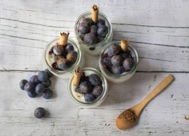 Homemade yogurt with blueberries on a white wooden table. View from above