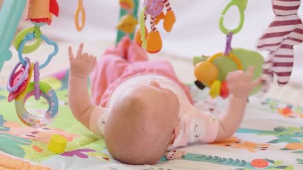 Fotografování novorozenců leží na posteli s barevným hračkama