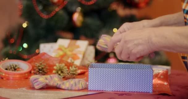 Babička balení dárek pro svou vnučku na Vánoce a Silvestr. Koncepce přípravy na Vánoce a Silvestr, vánoční strom pozadí