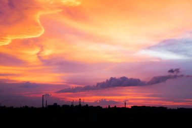 Bright purple, pink, lilac and orange sunset over city. City industrial landscape against the backdrop of the setting sun. Sunset with silhouette of city buildings and factory pipes with smoke