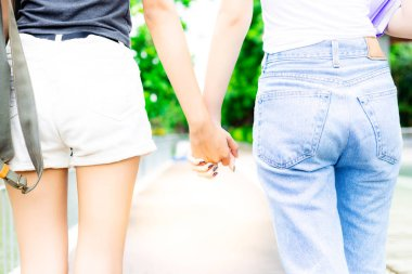 Lovely couple or friends is holding hands together during walking on the street at university. They homosexual. Beautiful women love and understand each other. Pretty girls wears shorts and jeans