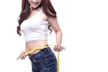 Charming beautiful woman gets satisfied of her body or figure. Attractive beautiful girl can lose weight quickly. Pretty woman can wear favorite jeans again. She use tape measure for measuring waist