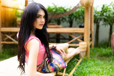Charming beautiful woman feel relaxing and happiness at home stay or resort. Attractive beautiful women wear thai style dress. Gorgeous woman has long weekend holiday and get vacation with happy face