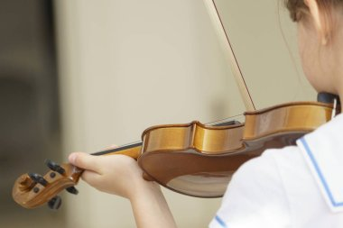 Girl playing violin in white room