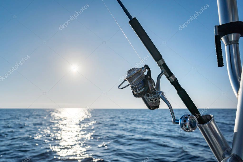 Fishing rod in a saltwater motor boat during fishery day in blue ocean. Successful fishing concept