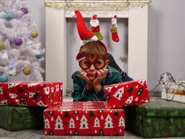 Boy in Santa hat and Christmas glasses sitting behind the Christmas gifts