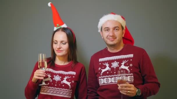 couple in santa hats clinking with champagne glasses and celebrating new year