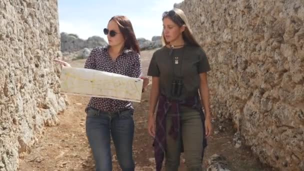 Two young girls walking with city map in the ancient city Lyrboton Kome in Turkey